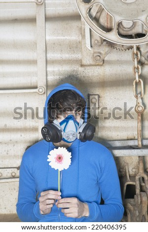 Young man wearing air filter mask and holding flower - stock photo