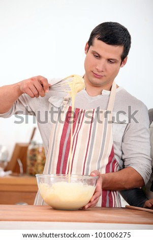 young man wearing an apron and doing dough - stock photo