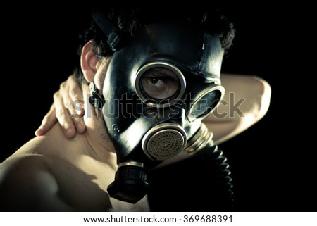 Young man wearing black rubber gas mask