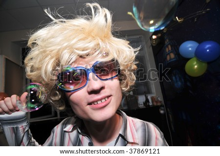 Young man wearing blond wig looks very drunk