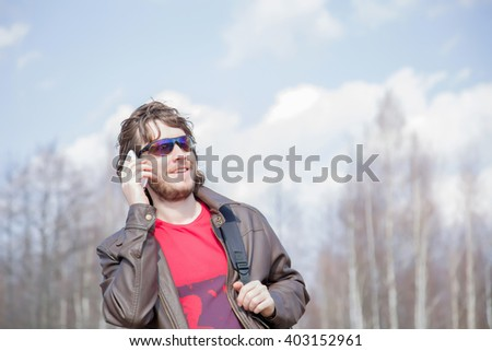 Young man wearing brown leather jacket and sunglasses, holding mobile phone, making a call and speaking on the phone. Man in spring day on claudy background.