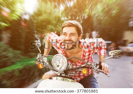 Young man wearing casual checkered shirt riding scooter on high speed on a summer day - stock photo