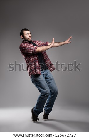 young man wearing  casual clothes avoiding something on grey background - stock photo