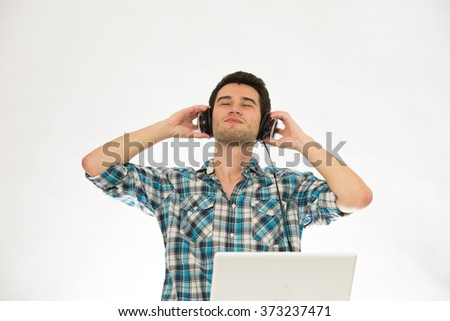 young man, wearing check shirt, listening music in headphones - stock photo
