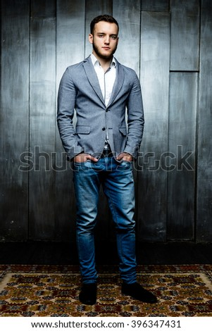 young man wearing elegant suit  on wooden background - stock photo