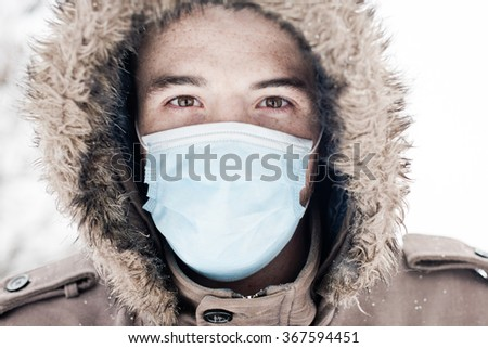 Young man wearing face mask, protection from virus infection in winter time - stock photo