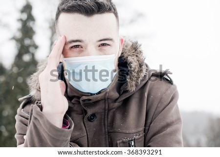 Young man wearing face mask, protection from virus infection in winter time, feeling bad with headache - stock photo