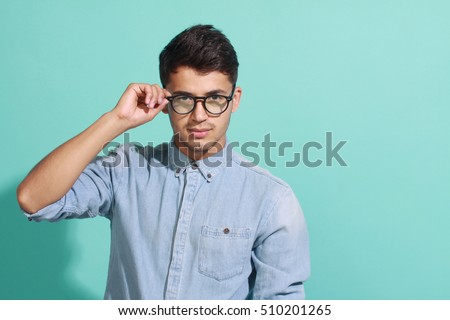 young man wearing glasses, posing on blue background