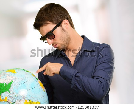 Young Man Wearing Goggle Showing Destination, Indoor - stock photo