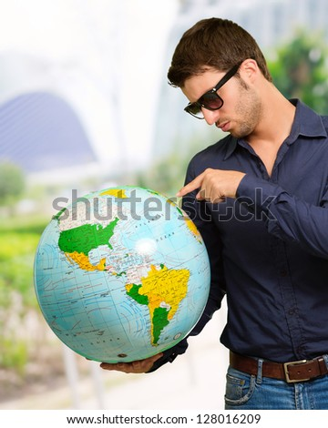 Young Man Wearing Goggle Showing Destination, Outdoor - stock photo