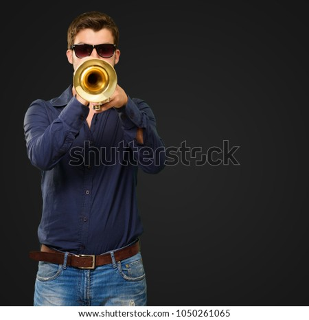 Young Man Wearing Goggles And Blowing Trumpet On Black Background