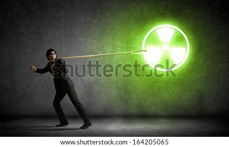 Young man wearing goggles pulling radioactivity symbol with rope - stock photo