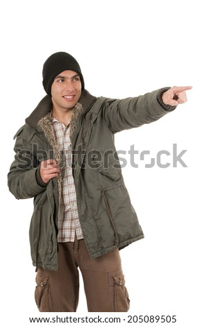 young man wearing green winter coat and a beanie pointing with finger isolated on white - stock photo