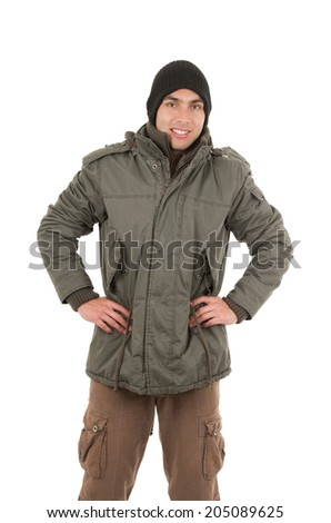 young man wearing green winter coat and beanie with hands on hips isolated on white - stock photo