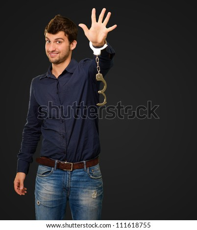 Young Man Wearing Handcuffs On Black Background - stock photo