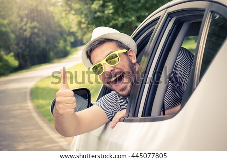Young man wearing hat and sunglasses showing thumbs up from driverâ??s seat through opened window. Vacation and travel concepts.  - stock photo
