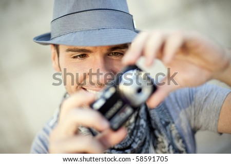 Young man wearing hat taking a picture using a camera - stock photo