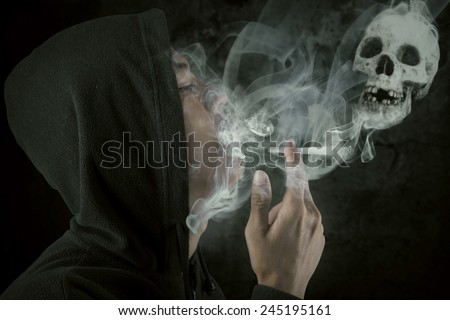 Young man wearing jacket smoking over a black background, shot in the studio - stock photo