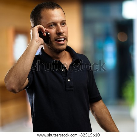 young man wearing polo shirt talking on mobile phone