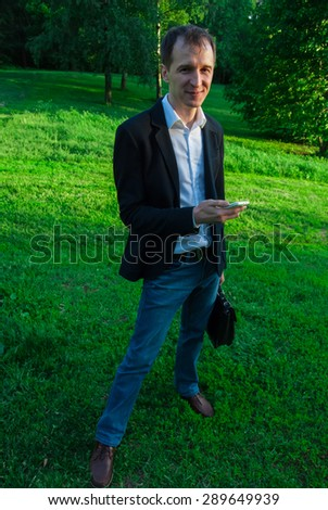 Young man wearing suit with smartphone, outdoors on the green background of trees and bushes. Business man in a green zone or park. An image for topics of finance, business and communication - stock photo