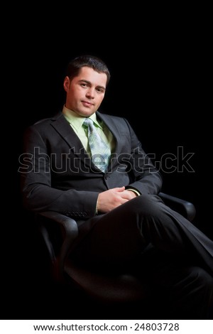 Young man wearing suit with tie sitting waiting - stock photo
