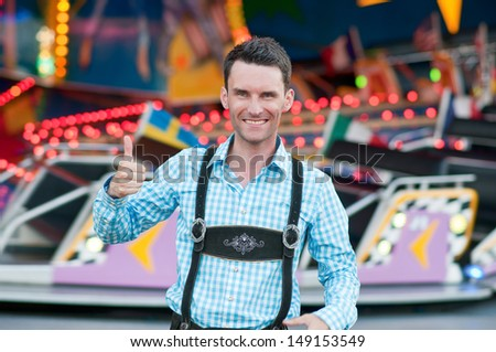 Young man wearing traditional Bavarian Lederhosen with thumbs up - stock photo