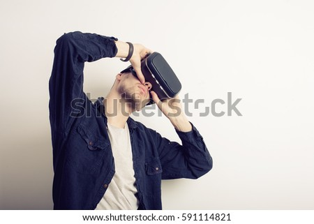 Young man wearing virtual reality headset or 3d glasses, standing against grey wall background