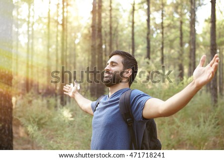 Young man welcoming the forest with open arms in a plantation while wearing casual clothing and a backpack