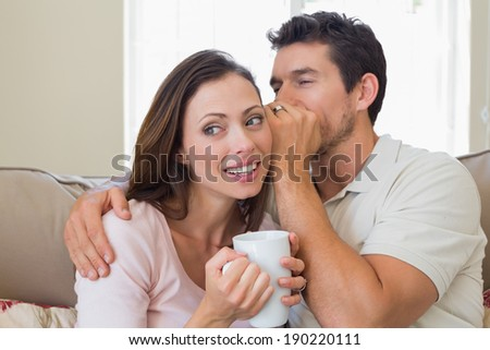 Young man whispering secret into a happy young womans ear in the living room at home - stock photo