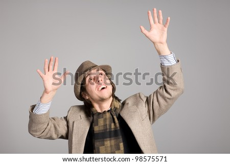 Young man who raised his hands in panic - stock photo