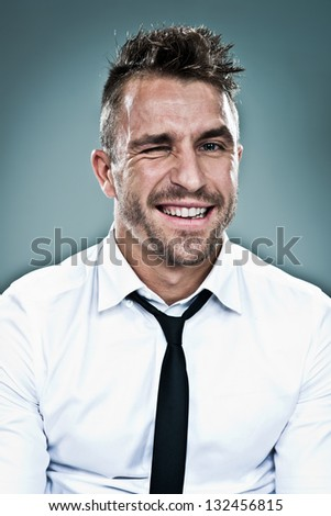 Young Man Winking over a Grey Background - stock photo