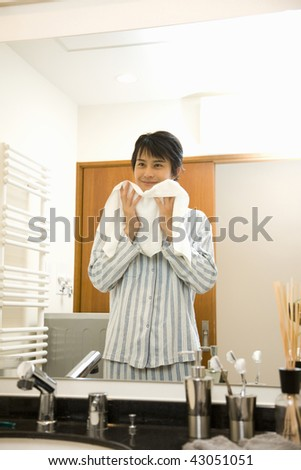 Young man wiping his face with towel - stock photo