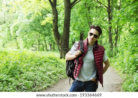 young man with a backpack walks in the forest - stock photo