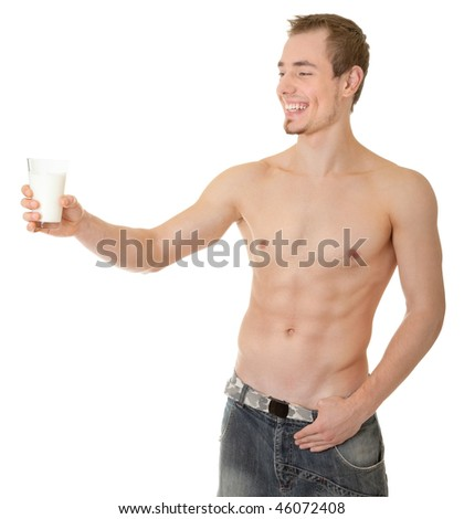 young man with a bare torso holding a glass of white liquid - stock photo