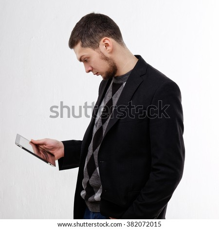 Young man with a beard holding a tablet on a white background. Dressed in a casual