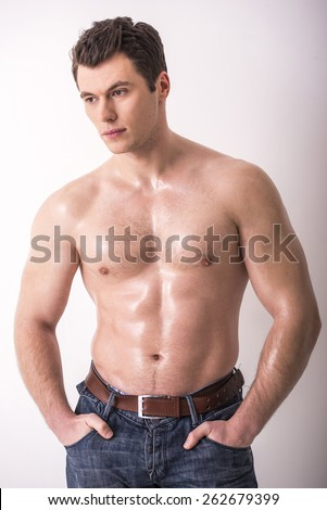 Young man with a beautiful physique is thinking on a white background.