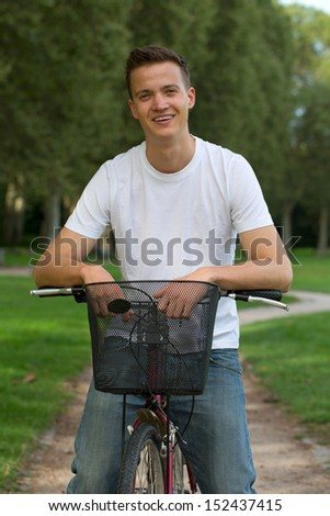 Young man with a bike on a path in a park