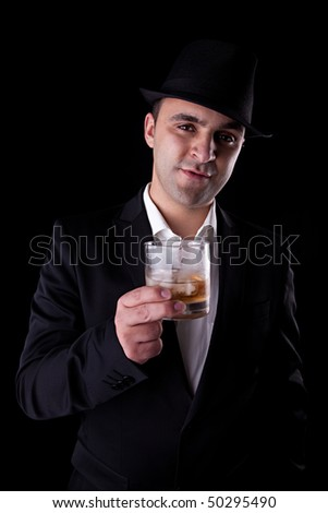 young man with a black hat and a glass of whiskey in his hand, isolated on black background - stock photo