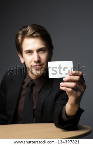 Young man with a business card - stock photo