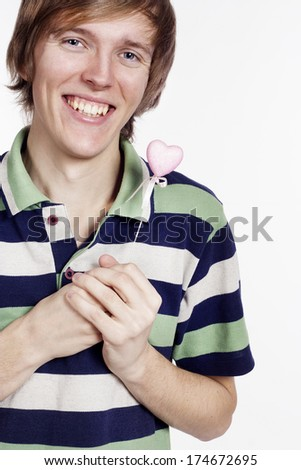 Young man with a candy  heart in his hands - stock photo