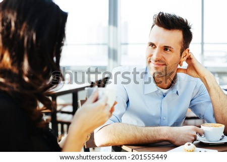 Young man with a cappuccino in his hand enjoying a conversation with a woman - stock photo