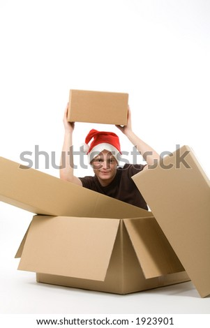 young man with a christmas cap sits in a carton and lift up another one blank package (blank for your own text)
