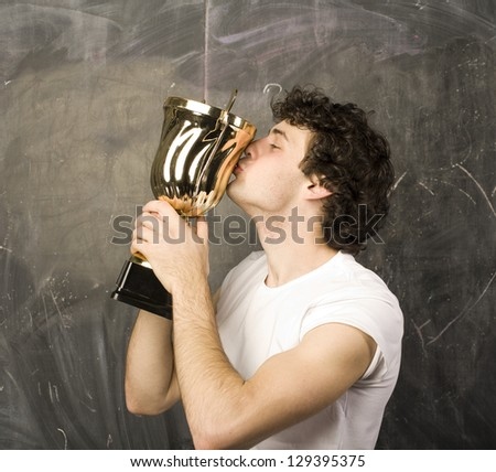young man with a golden cup against blackboard - stock photo