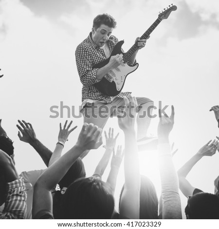 Young Man with a Guitar Performing on an Ecstatic Crowds - stock photo