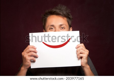 Young man with a happy smiley card half covering face - stock photo