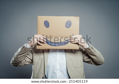 Young man with a happy smiley card half covering face
