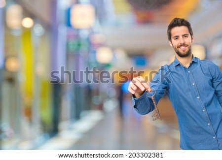 young man with a key in a shopping center
