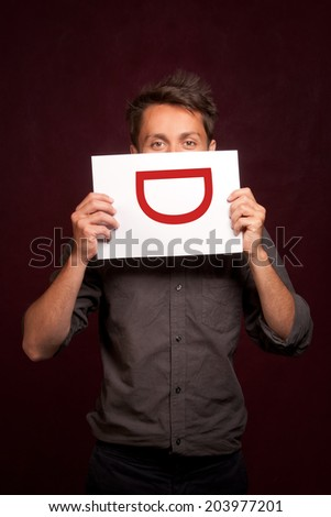 Young man with a laughing smiley sign on a sheet of paper half covering face - stock photo