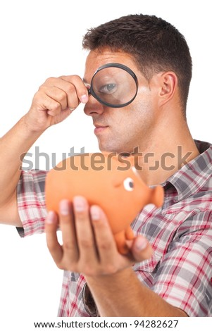 young man with a magnifying glass and holding a piggy bank - stock photo
