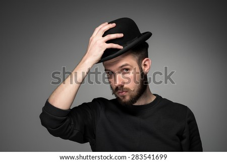 Young man with a mustache and beard raising his hat  in respect and admiration for someone. portrait on gray background.  - stock photo